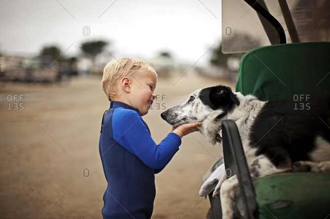 Young boy with his pet dog at the beach.