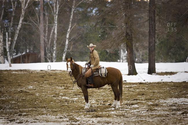 Man on horseback in a snowy field.