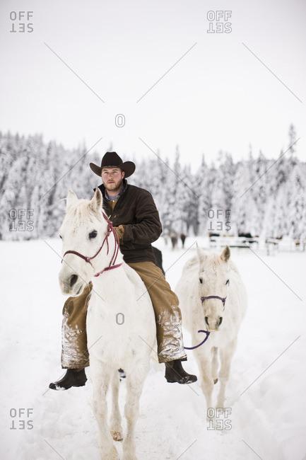 Cowboy on horseback leading another horse.