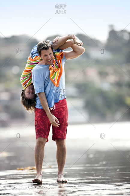 Father playing with his son on the beach.