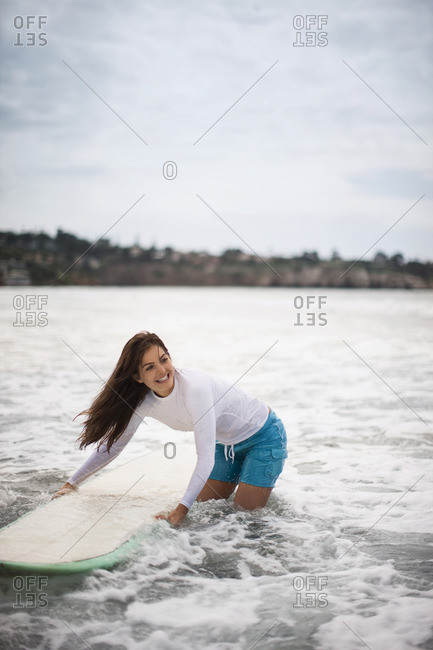 Young woman carrying her surfboard into the ocean.