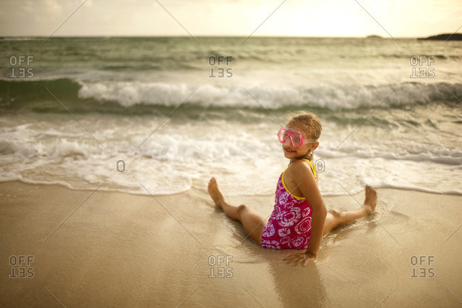 Young girl sitting on the beach at the water's edge.