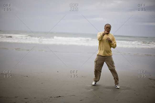 Man shadow boxing on the beach.