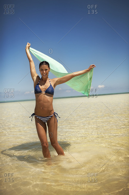 Young woman holding her sarong up at the beach.