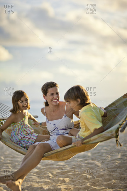 Mother and her two children having fun on a hammock at the beach.