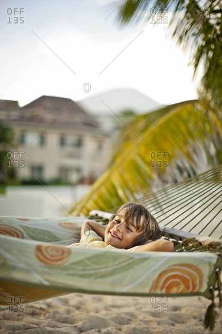 Smiling young boy lying in a hammock at the beach.