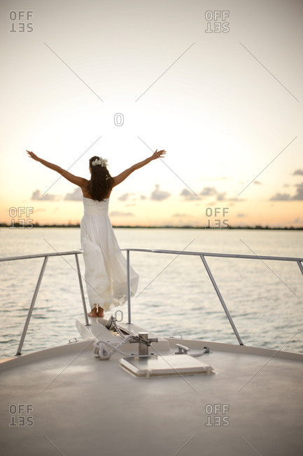 Bride standing at the bow of a boat.