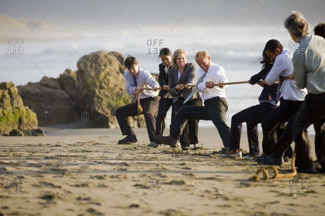 Group of businesspeople playing tug of war on the beach.