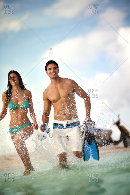 Young couple running into the ocean to go snorkeling.