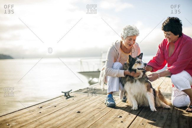 Two senior women petting their dog on a pier.