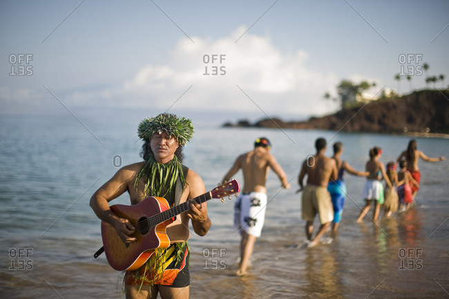 Man in traditional dress playing guitar on the beach for tourists.