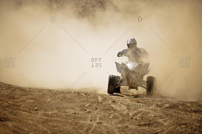 Quad bike rider riding on the dirt.