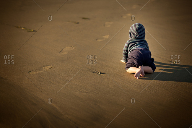 Baby boy crawling on the sand.