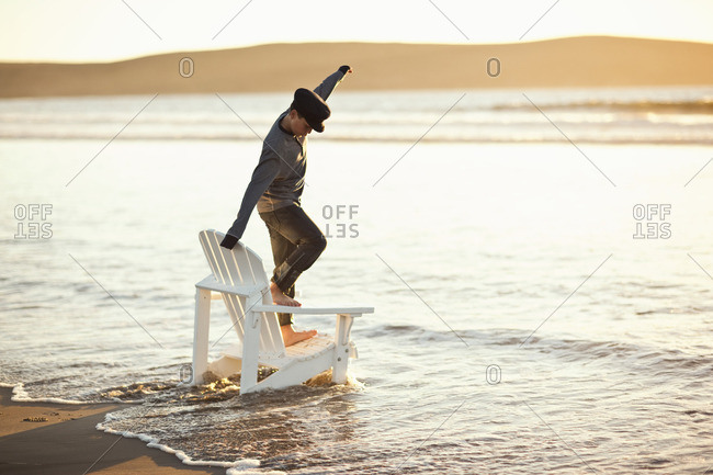 Young boy balancing on a chair as the tide comes in at the beach.