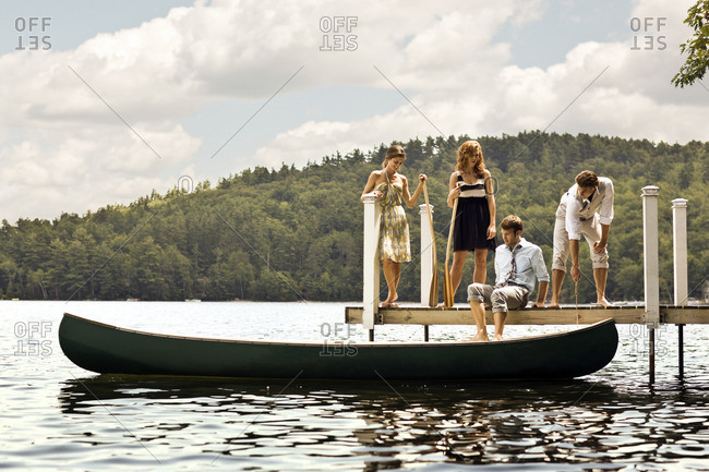 Group of friends on a pier ready to board a canoe.