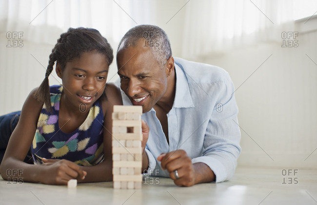 Father and daughter playing a block stacking game.