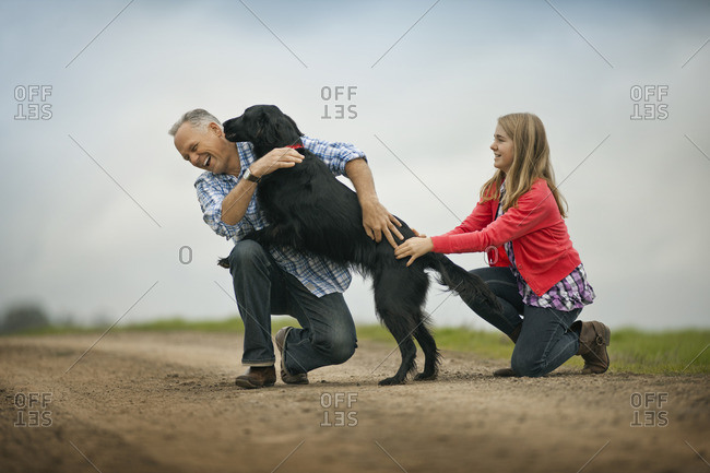 Father and daughter playing with their dog.
