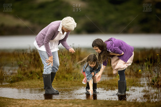 Senior woman exploring the shallows of a lake with her two granddaughters.