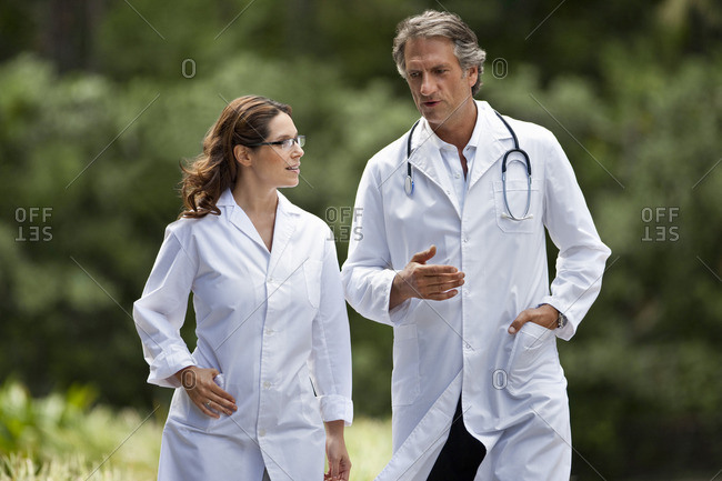 Two doctors walking together outside.