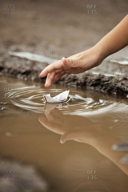 Paper boat floating on a puddle.