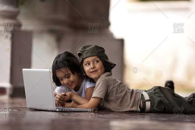 Two children using a laptop.