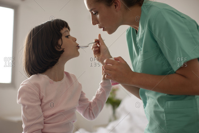 Nurse giving a young patient a dose of medicine.