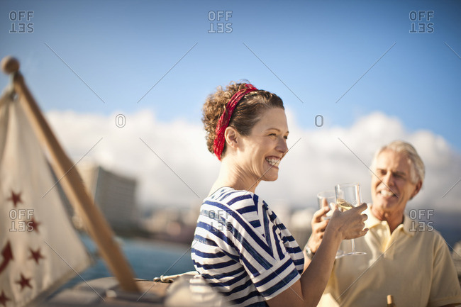 Couple toasting with wine on a boat.
