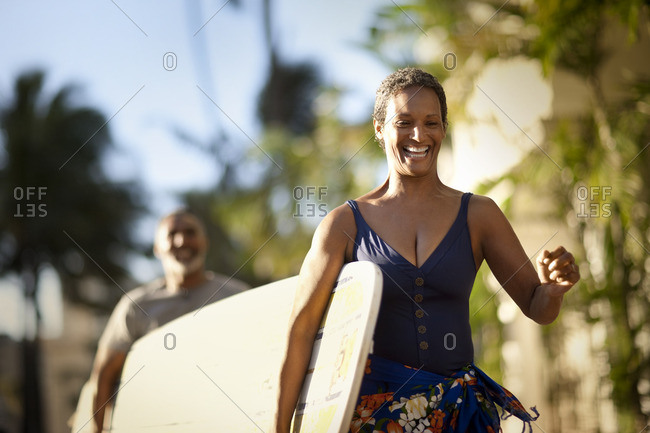 Couple carrying their surfboard to the beach.