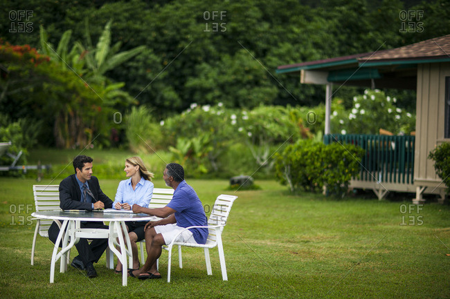 Businesspeople sitting in a garden having a discussion.
