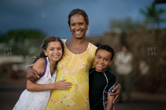 Smiling woman with her arm around her two children.
