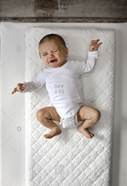 Crying baby lying on a blanket.