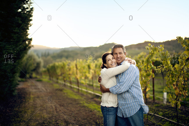 Couple hugging in a vineyard.