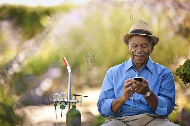 Senior man on breathing apparatus using a cellphone.