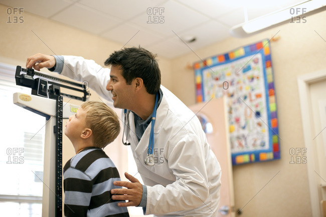 Doctor measuring a young patient's growth.