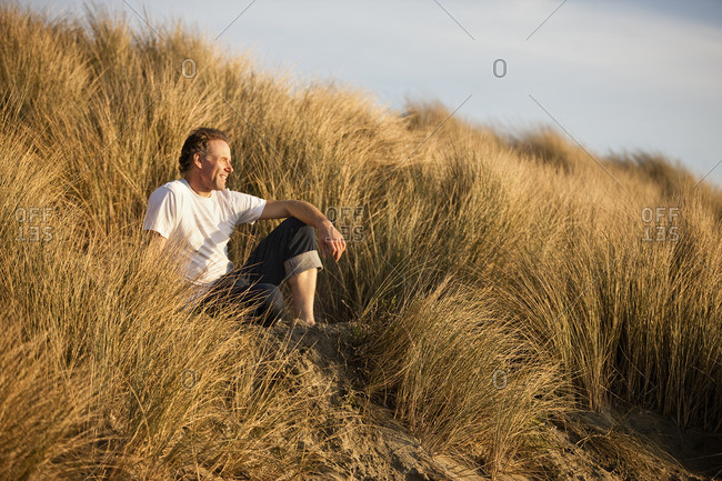 Smiling man sitting on a grassy sand dune.