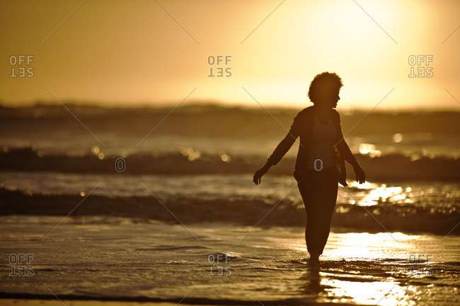 Woman walking in the shallow water at the beach.