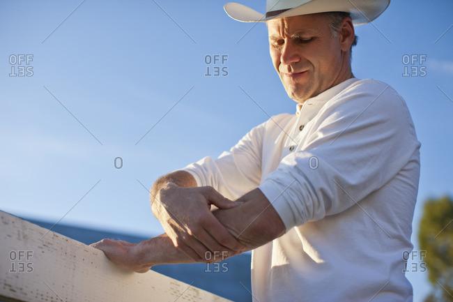 Farmer leaning on a fence.