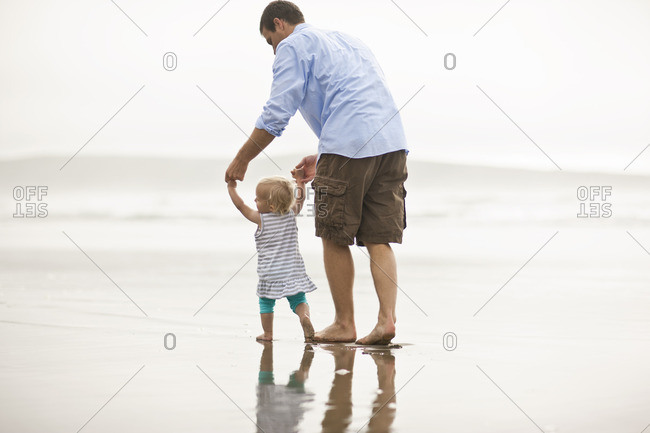 Father helping his toddler to walk on the beach.