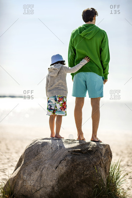 Father and son standing on a boulder at the beach.