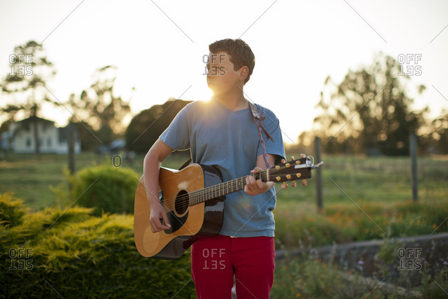 Young boy playing the guitar.
