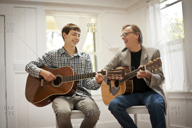 Father and son playing the guitar together.