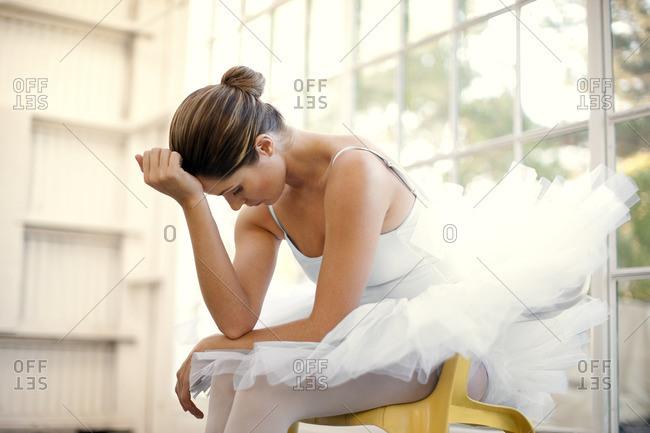 Ballet dancer sitting resting her head on her hand.