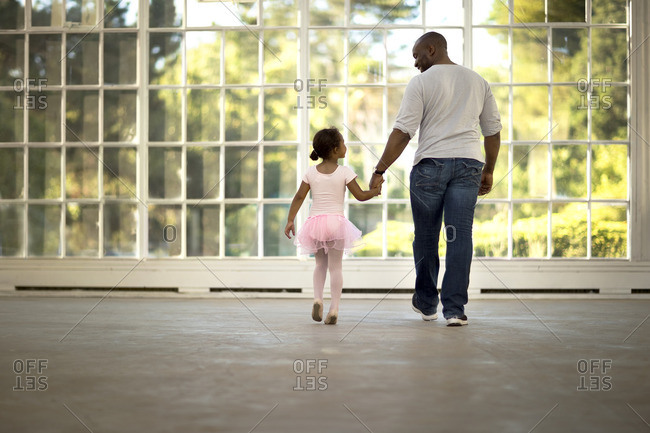 Father walking his young daughter into her ballet class.