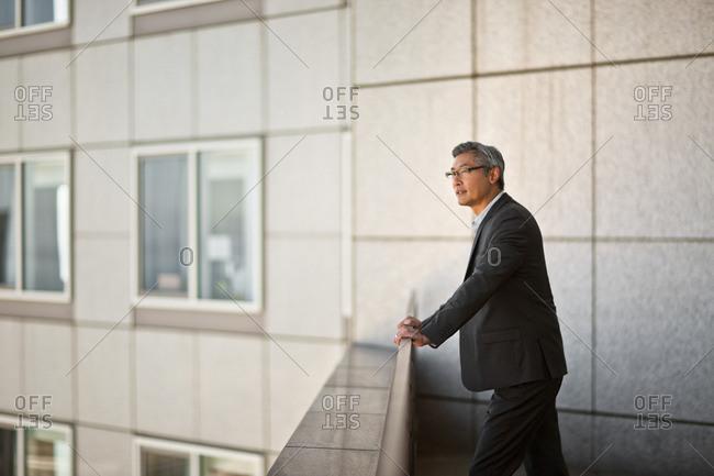 Businessman taking a break on his office balcony.