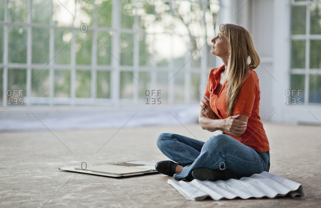 Woman sitting in an unfurnished home with fabric samples.