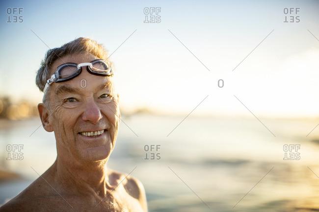 Smiling senior man wearing goggles at the beach.