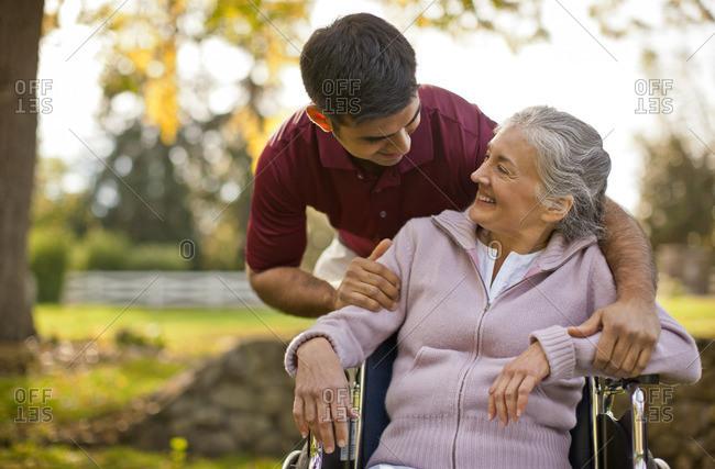 Man caring for a senior woman in a wheelchair.