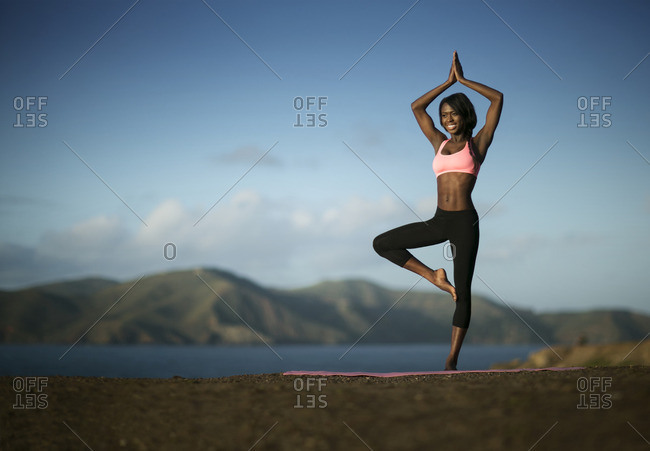 Young woman practicing yoga by a lake.