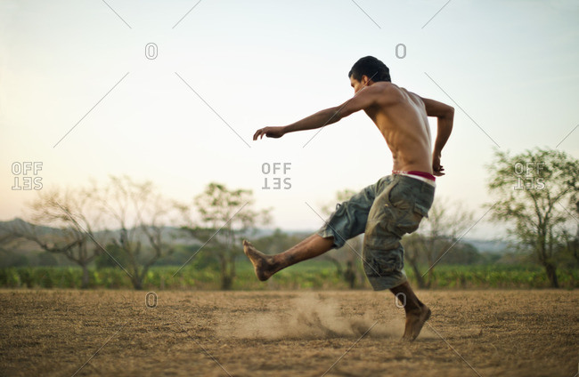 Young man kicking on a dusty field.