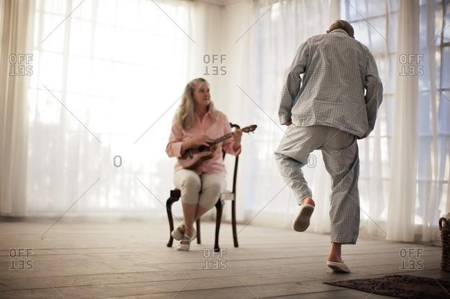 Senior woman playing the guitar, as her husband dances along.